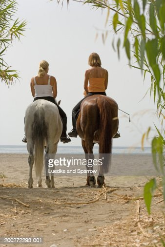Two women on horses on beach, rear view : Stock Photo
