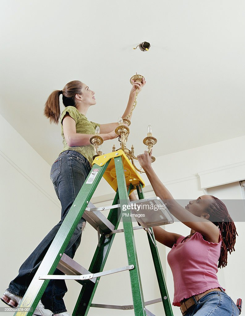 Two women on ladder hanging light fixture to ceiling : Stock Photo