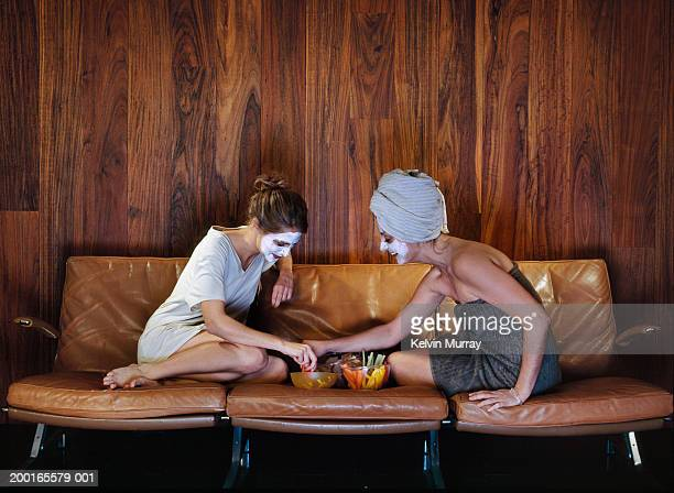 Two women on sofa with food, wearing beauty masks
