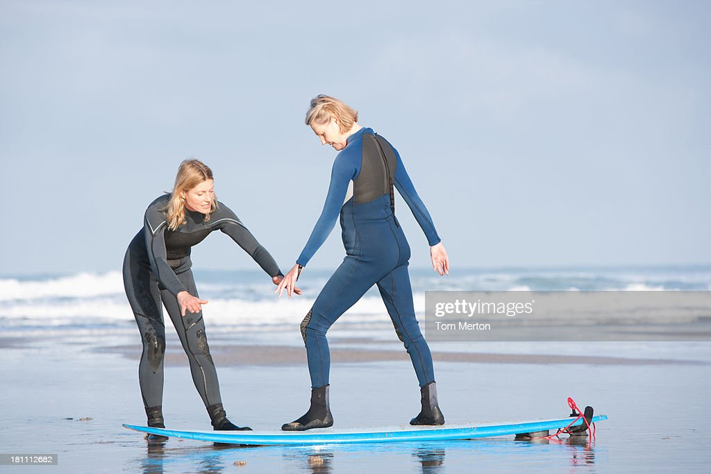 Two women on the beach with surfboards : Stock Photo
