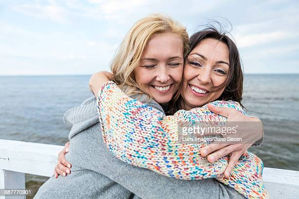 Two women on the waterfront embracing