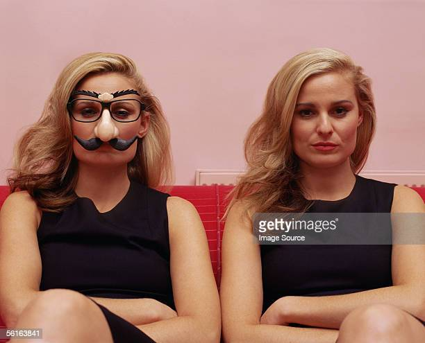 Two women one wearing a comedy disguise