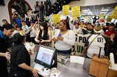 Two women order food as striking fast food workers home healthcare workers and their supporter shout slogans inside a MCDonalds during a rally and...