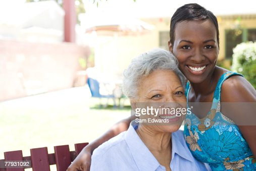 Two women outdoors on wooden bench