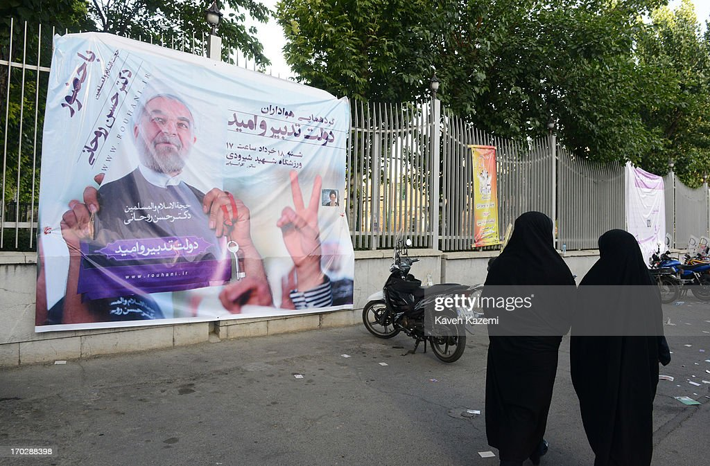 Two women pass by a banner with picture of Hassan Rowhani, one of the eight candidates approved to run for the Iranian presidency outside Shiroudi stadium on June 8, 2013 in Tehran, Iran. Iran is to go to the polls for the Iranian general election on June 14, 2013.