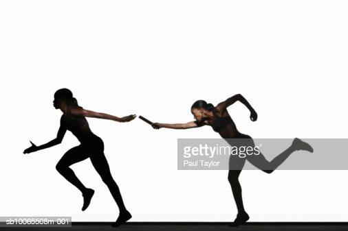 Two women passing relay baton