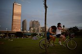 Two women pedal a tandem bicycle in a park near the Han river in Seoul at dusk on August 1 2014 South Korea's state weather agency issued a heat wave...