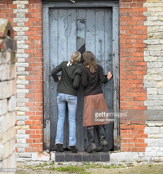 Two women peeking through window in door, rear view