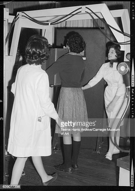Two women performing chest xray on woman at HealthORama fair circa 19551975