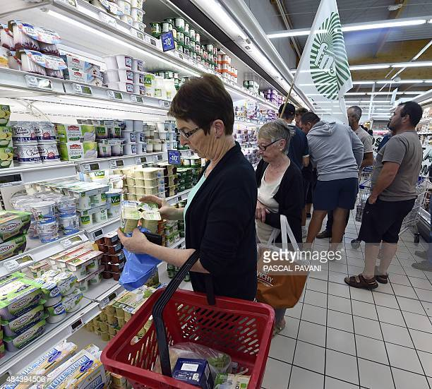 Two women peruse the fridge shelves as farmers stick stickers on consummer goods reading in French 'Made with milk sold at loss Farmers strangled...