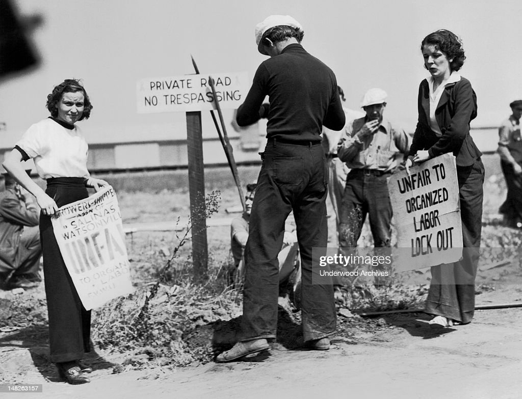 Two women picket a company man digging a fence post hole to help barricade a lettuce processing plant Salinas California September 25 1936