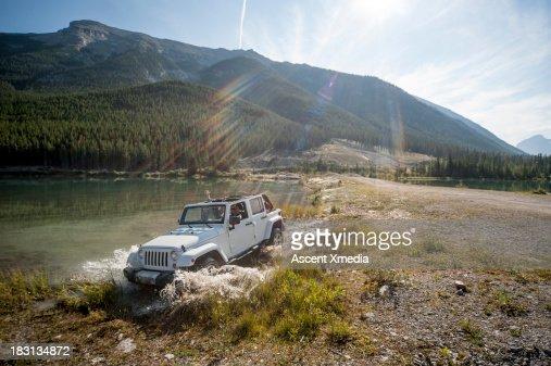 Two women pilot Jeep through lake shallows, mtns