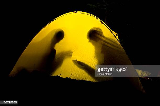 Two women play cards at night silhoutted against their tent walls.