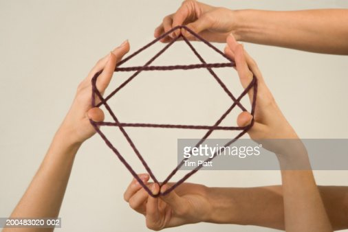 Two women playing cat's cradle, close-up : Stock Photo