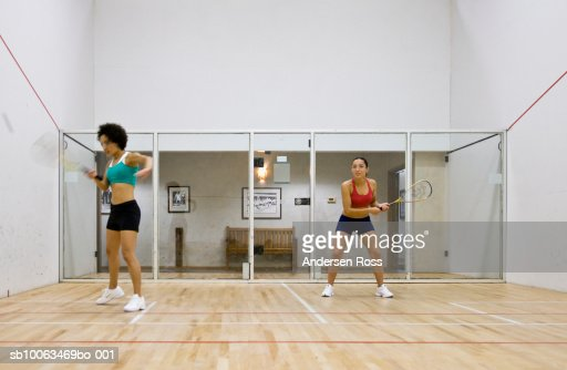 Two women playing racquetball in indoor court (blurred motion)