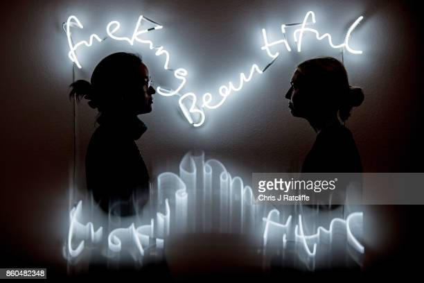 Two women pose for photographs next to fuckingbeautiful by Time Noble and Sue Webster estimated at £25000£35 during an Art for Grenfell press call at...