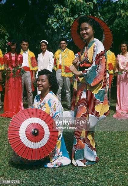 Two women pose in traditional dress during Aloha Week in Hawaii circa 1960