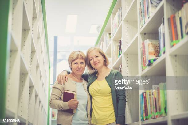 Two women posing in the library