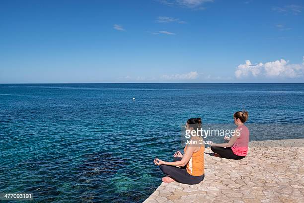 Two women practice yoga from a waterfront ledge