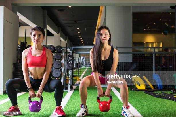 Two women practicing kettlebell snatches in gym