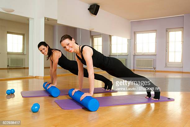 Two women practicing with pilates rolls in a health club