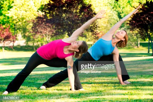 Two women practising yoga together in a park