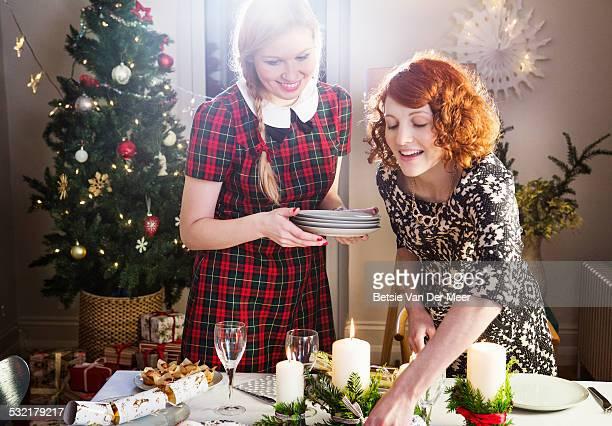 Two women preparing table for Christmas dinner.