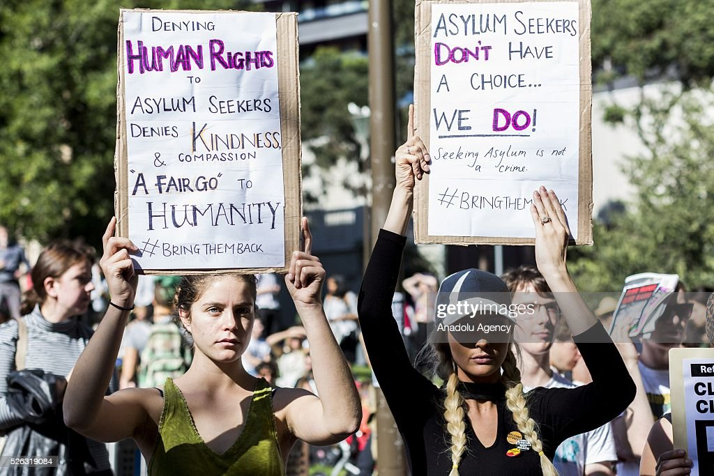 Two women protestors hold banners during a protest demanding that asylum seekers held in off shore detention to be brought to Australia at a rally in Melbourne, Australia on April 30, 2016. Protests have started after The Papua New Guinean Supreme Court ruled that the Australian-run detention centres on Manus Island were illegal and unconstitutional.