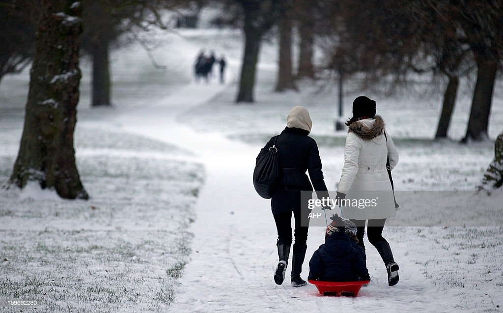 Two women pull a sledge through Primrose Hill in Regent's Park after snowfall in central London on January 18, 2013. Snow swept across Britain, forcing airports to cancel hundreds of flights and more than 3,000 schools to close. AFP PHOTO/ANDREW COWIE