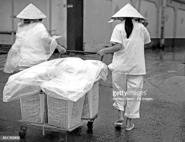 Two women pull a trolley during a rain shower in Ho Chi Minh City Vietnam