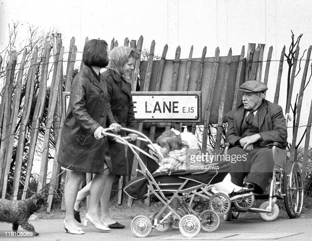 Two women pushing baby girls past an elderly man in a wheelchair on Vicarage Lane West Ham east London circa 1970
