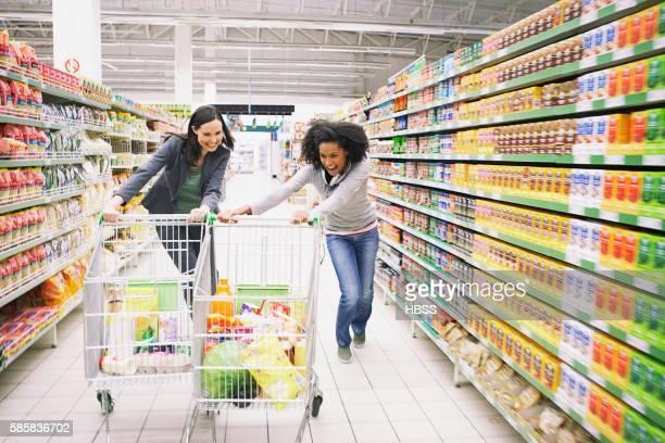 Two women pushing shopping carts