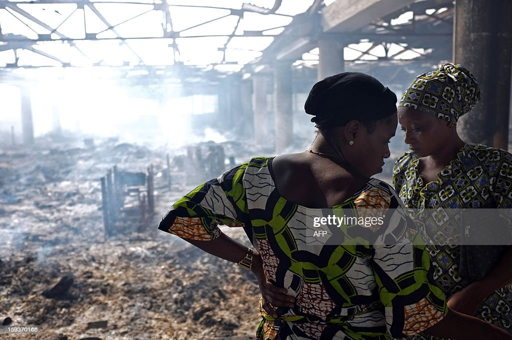 Two women react on January 12, 2013 to the destruction of Lome's Grand Marche (''Big Market'') after it was engulfed in flames late on January 11. AFP Photo / Daniel Hayduk