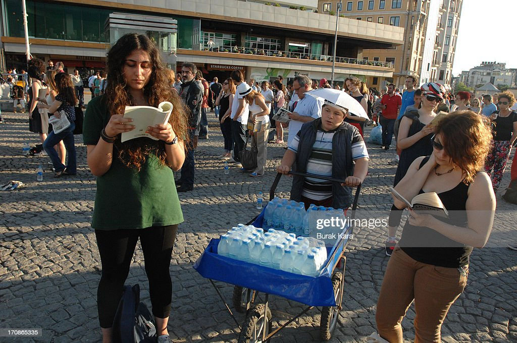 Two women read as a vendor walks past during a silent protest in Taksim Square June 19, 2013 in Istanbul, Turkey. Performance artist Erdem Gunduz, nicknamed 'The Standing Man,' became a new symbol of the anti-government protests after a eight-hour vigil in Taksim Square. Gunduz reportedly said he was protesting in solidarity with demonstrators after they were evicted from Gezi Park that adjoins Taksim Square. The protests began in May, with environmentalists upset over plans to build in Gezi Park, and has grown into a broader demonstration against Prime Minister Tayyip Erdogan's government.