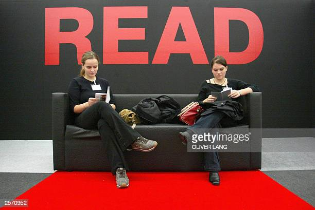 Two women read books in a sofa at the Frankfurt Book Fair 08 October 2003 The fair the biggest event in the publishing world calendar opened 07...