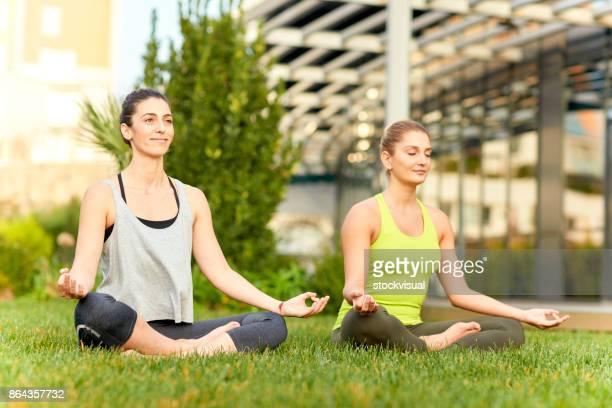 Two women relaxing doing yoga on grass