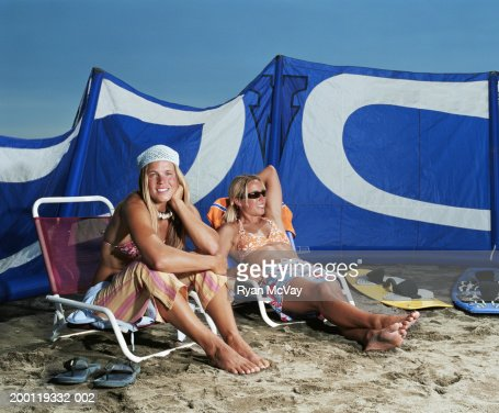 Two women relaxing in beach chairs, kiteboarding gear in background : Stock Photo