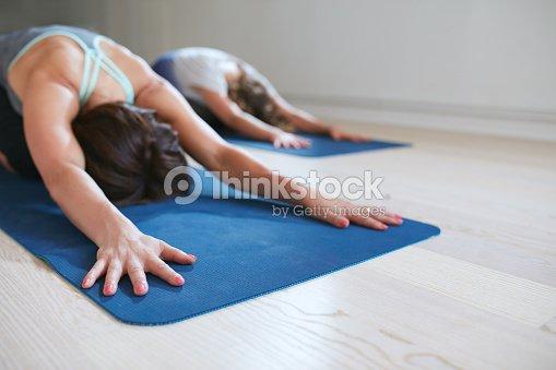 Dos Mujeres Relajante En Niño Haciendo Yoga Pose Foto de stock ... e413d6fb7616