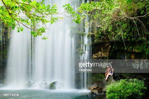 Two women relaxing next to a waterfall.