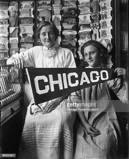 Two women residents of Chicago's South Side neighborhood show their pride and urban spirit by holding up a Chicago pennant ca1910s