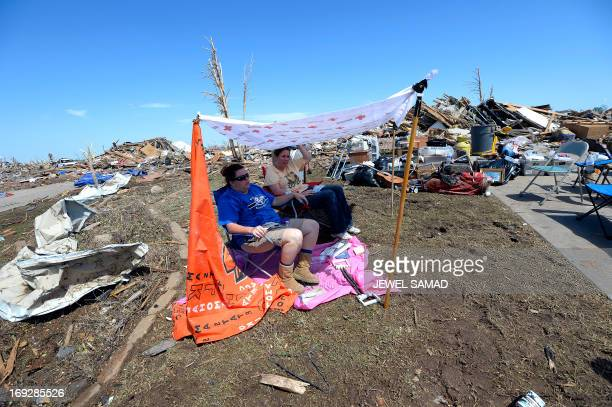 Two women rest under a makeshift tent at their tornado devastated home on May 22 2013 in Moore Oklahoma As rescue efforts in Oklahoma wound down...