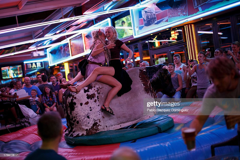 Two women ride a rodeo bull machine at a pub around the British Square on August 9, 2013 in Benidorm, Spain. Benidorm is one of Europe's top package holiday destinations and one of Spain's busiest tourist destinations. The Costa Blanca hotspot of Benidorm is calculated to have a population of around 72,000, which is estimated to rise to more than 300,000, during the summer months as the tourists and visitors flock to its popular beaches.
