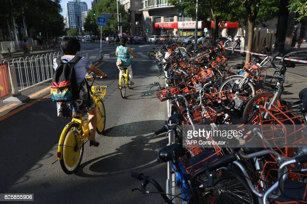 Two women ride in a car lane past a stack of shared bicycles blocking the cycle lane on a street in Beijing on August 3 2017 China on August 3 issued...