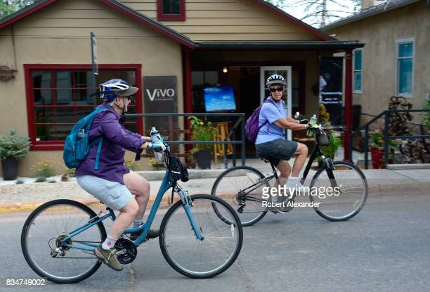 Two women ride their bicycles along Canyon Road home to dozens of art galleries in Santa Fe New Mexico
