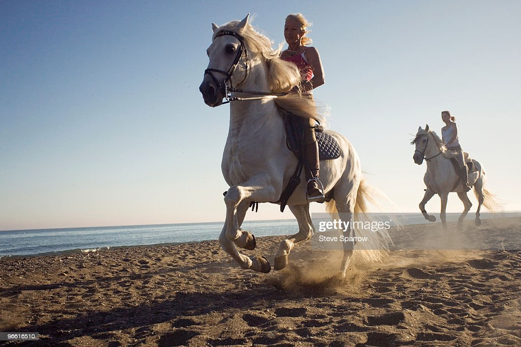 Two women riding horses on beach