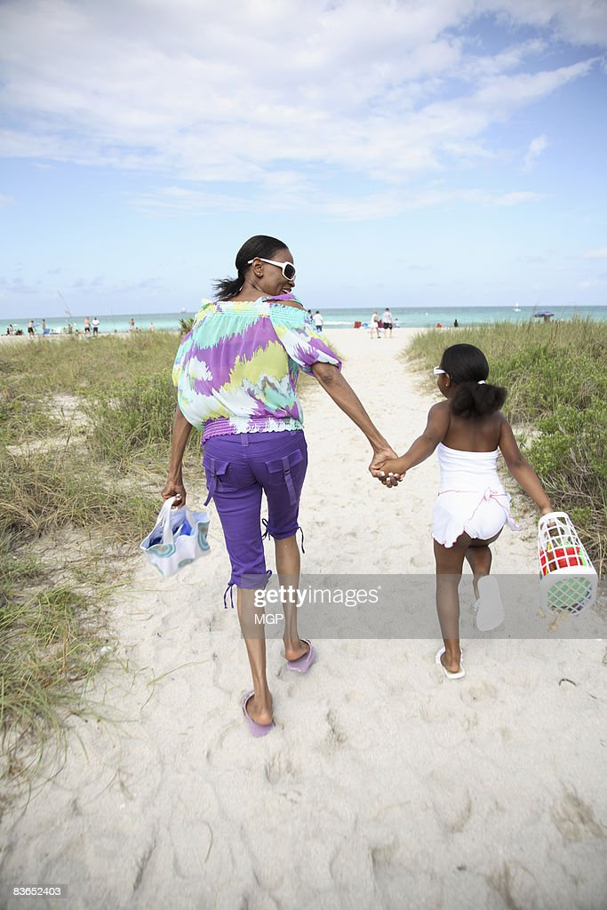 two women run toward beach : Stock Photo