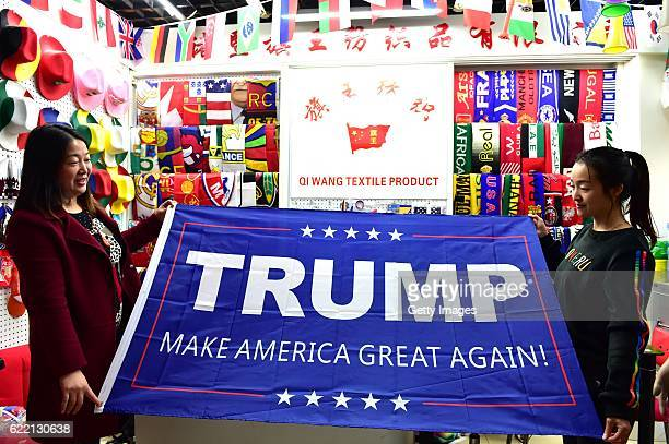 Two women running business of banners pose with a support banner for Republican presidential candidate Donald Trump at Yiwu International Trade...