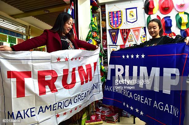 Two women running business of banners pose with support banners for Republican presidential candidate Donald Trump at Yiwu International Trade Centre...
