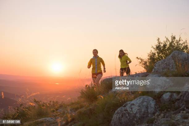 Two women running in nature against dramatic sky during sunset