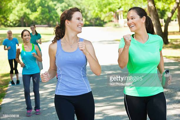 Two women running together at a park